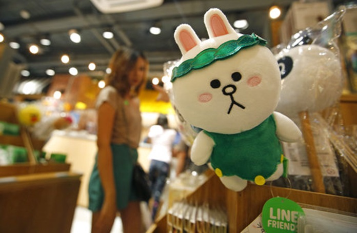 A customer selects merchandise at Line Village in Bangkok, Thailand, Thursday, June 22, 2017. (AP Photo/Sakchai Lalit)