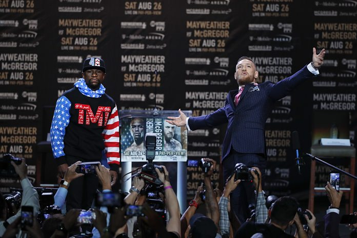 Floyd Mayweather Jr., left, and Conor McGregor pause for photos during a news conference at Staples Center on Tuesday, July 11, in Los Angeles. The two will fight in a boxing match in Las Vegas on Aug. 26. (AP Photo/Jae C. Hong)