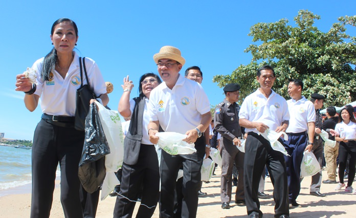 """Tourism and Sports Minister Kobkarn Wattanavrangkul (left) helps collect garbage off Pattaya Beach to raise awareness for """"green tourism""""."""
