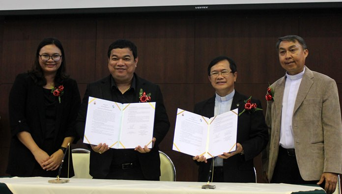(L to R) Eakarin Sangdhammarath and Kritchon Phumkittipit sign an agreement with Rev. Picharn Jaiseri and Rev. Peter Pattarapong Srivorakul to develop a new electric wheelchair and customized cushions for the disabled.