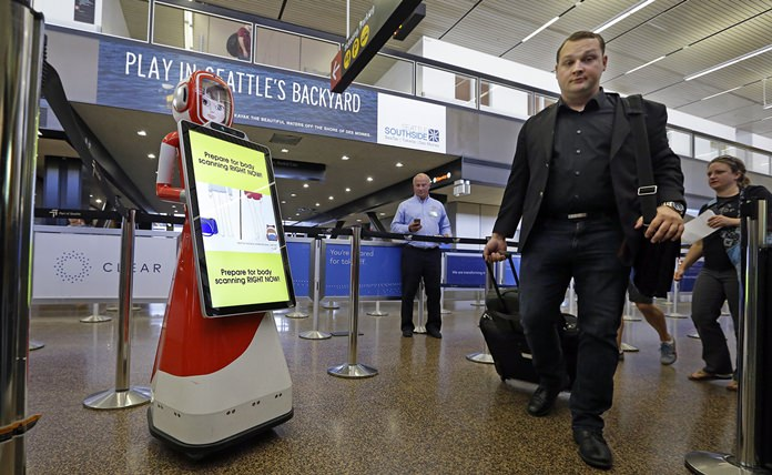 Airline passengers walk past a robot providing tips for getting through security faster during a pilot project as they head toward a security checkpoint Tuesday, July 11, 2017, at Seattle-Tacoma International Airport, in SeaTac, Wash. (AP Photo/Elaine Thompson)
