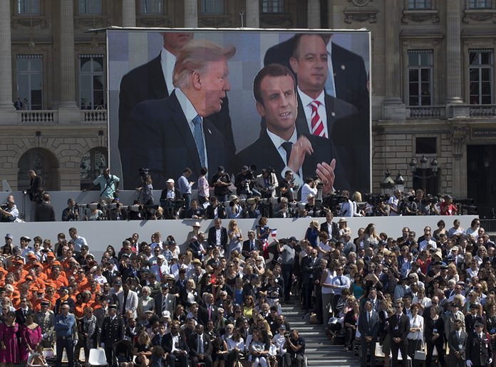 President Donald Trump, French President Emmanuel Macron and White House Chief of Staff Reince Priebus are seen on a large video screen during Bastille Day parade on the Champs Elysees avenue in Paris, Friday, July 14, 2017. (AP Photo/Carolyn Kaster)