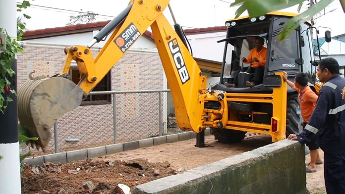 Workers used heavy machinery to knock down a barrier and dig out a trench to let the trapped water escape.