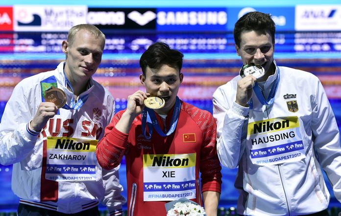 Bronze medalist Ilya Zakharov of Russia, gold medalist Xie Siyi of China and silver medalist Patrick Hausding of Germany, pose with their medals after the men's diving 3m springboard final of the 17th FINA Swimming World Championships in Budapest, Hungary, Thursday, July 20. (Zoltan Mathe/MTI via AP)