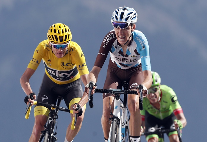 Britain's Chris Froome, wearing the overall leader's yellow jersey, left, Colombia's Rigoberto Uran, right, and France's Romain Bardet cross the finish line during the eighteenth stage of the Tour de France cycling race on the Izoard pass, France, Thursday, July 20. (AP Photo/Christophe Ena)