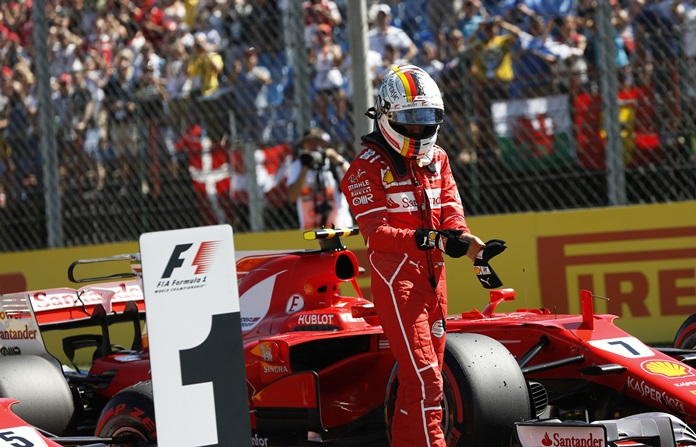 Ferrari driver Sebastian Vettel of Germany walks away from his car after he clocked the fastest time during the qualifying session for the Hungarian Formula One Grand Prix, at the Hungaroring racetrack in Mogyorod, northeast of Budapest, Saturday, July 29. (AP Photo/Darko Bandic)