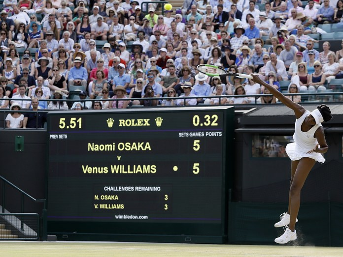 Venus Williams of the United States serves to Japan's Naomi Osaka during their Women's Singles match at the Wimbledon Tennis Championships in London Friday, July 7. (AP Photo/Kirsty Wigglesworth)