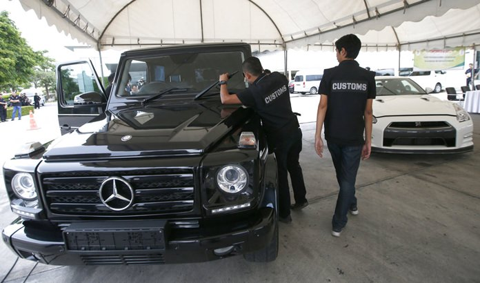 Thai Customs officers check seized Mercedes GLE 350, left, and Nissan GTR during a press conference at the customs office in Bangkok, Thailand, Friday, June 30, 2017.(AP Photo/Sakchai Lalit)