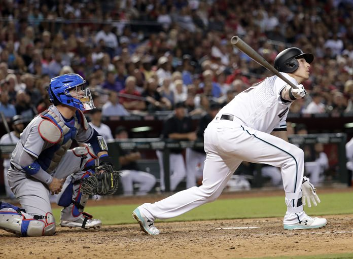 Arizona Diamondbacks Jake Lamb follows through on a grand slam during the seventh inning of a baseball game as Los Angeles Dodgers catcher Yasmani Grandal looks on, Tuesday, Aug. 8, in Phoenix. (AP Photo/Matt York)