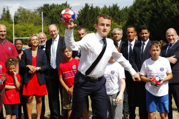 French President Emmanuel Macron throws a ball as he visits a recreation center in Moisson, east of Paris, France, Thursday, Aug. 3. (Philippe Wojazer/Pool Photo via AP)