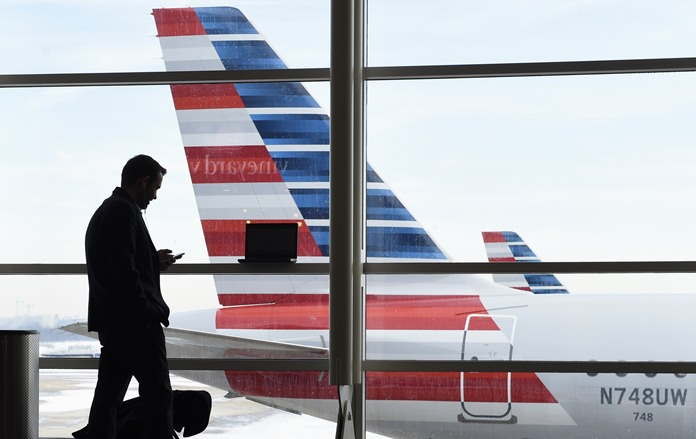 In this Jan. 25, 2016, file photo, a passenger talks on the phone as an American Airlines jets sit parked at their gates at Washington's Ronald Reagan National Airport. Ten people were injured last weekend as an American Airlines flight plowed through turbulence on its way to landing in Philadelphia. (AP Photo/Susan Walsh, File)