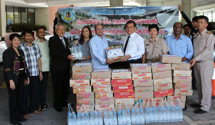 Bangladesh Association of Pattaya President Jahangir Hossain presents donated drinking water and dried food to Pattaya Deputy Mayor Vichien Pongpanit to be passed on to agencies aiding victims in Kalasin, Maha Sarakham, Nakhon Ratchasima, Sakon Nakhon and Yasothon.