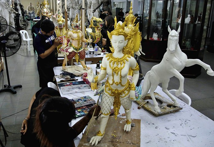 Volunteers paint statues of deities and creatures from ancient Indian epics to decorate the royal crematorium at the Fine Arts Department in Bangkok.
