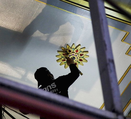 A worker installs a golden plate on the ceiling to decorate one of the buildings at the royal crematorium for HM the late King Bhumibol Adulyadej in Sanam Luang, Bangkok.