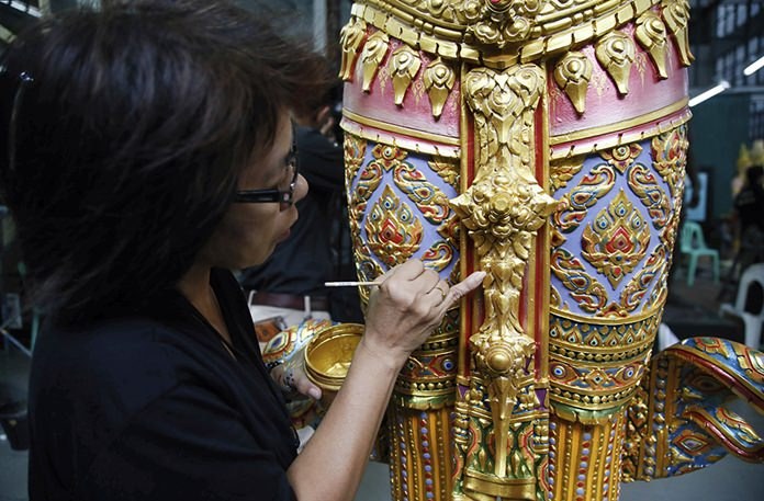 An artist paints a standing angel statue from ancient Indian epics to decorate the royal crematorium at the Fine Arts Department in Bangkok. Preparations for Construction work on the huge ceremonial crematorium is ahead of schedule, according to the country's Fine Arts Department.