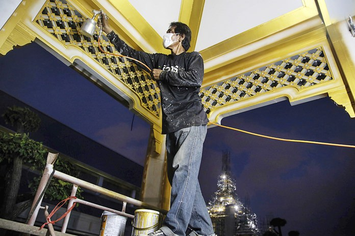 A worker paints the roof of one of the buildings at the royal crematorium in Sanam Luang.