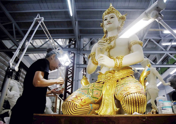 A volunteer paints a sitting angel statue from ancient Indian epics to decorate the royal crematorium.