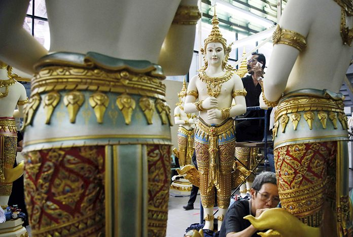 Volunteers paint standing angel statues from ancient Indian epics.