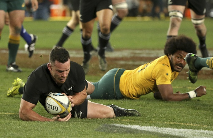 New Zealand's Ryan Crotty, left, scores a try against Australia during their rugby union test match in Sydney, Saturday Aug. 19. (AP Photo/Rick Rycroft)