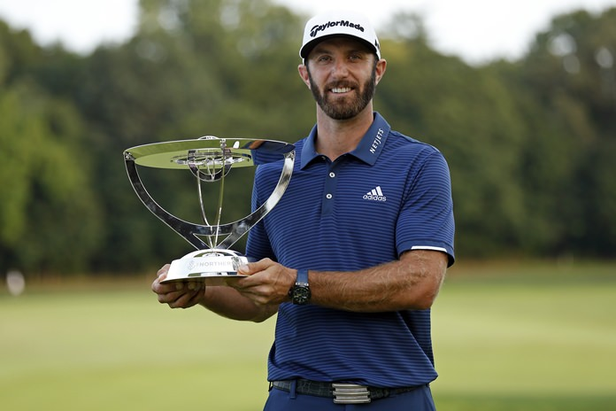 Dustin Johnson holds up his trophy after winning The Northern Trust golf tournament over Jordan Spieth in a playoff on Sunday, Aug. 27, in Old Westbury, N.Y. (AP Photo/Adam Hunger)