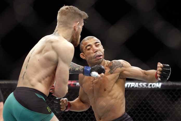 In this Dec. 12, 2015, file photo, Conor McGregor, left, fights Jose Aldo during their featherweight championship mixed martial arts bout at UFC 194 in Las Vegas. (AP Photo/John Locher)