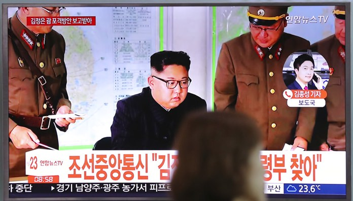 A woman walks by a TV screen showing a local news program reporting about North Korean military's plans to launch missiles into waters near Guam, with an image of North Korean leader Kim Jong Un, at Seoul Train Station in Seoul, South Korea, Tuesday, Aug. 15, 2017. (AP Photo/Lee Jin-man)
