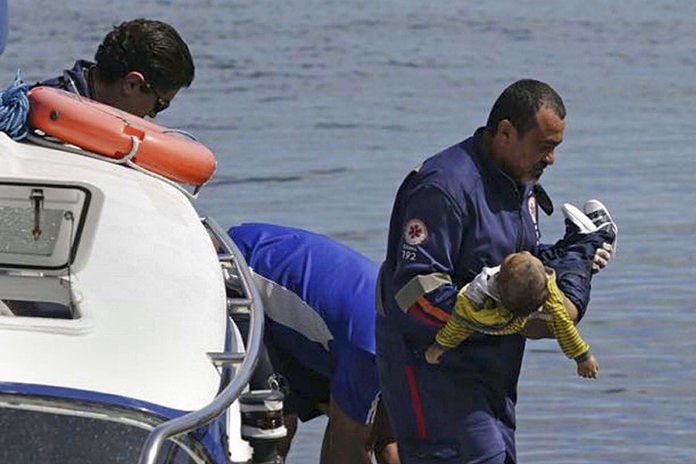 A rescue worker carries an unconscious 1-year-old to a waiting ambulance. (Xando Pereira/A Tarde/Futura Press via AP)