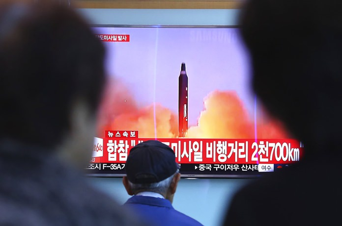 People watch a TV screen showing a file footage of North Korea's missile launch, at the Seoul Railway Station in Seoul, South Korea, Tuesday, Aug. 29, 2017. (AP Photo/Ahn Young-joon)