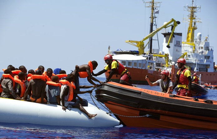 Rescuers from NGO Open Arms conduct a rescue operation in the waters some 25 Nautical miles (29 miles, 46 kilometers) north of the Libyan coast, Sunday, Aug. 27, 2017. Some 120 migrants were rescued during the operation. (AP Photo/Darko Bandic)