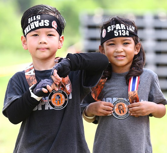 Two young Spatans proudly show off their race medals.