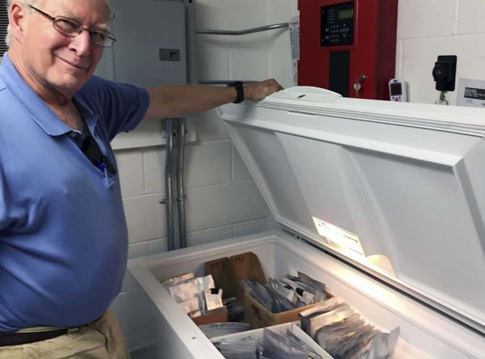 "In this Aug. 31, 2017 photo, Bill Brumback, director of conservation at the New England Wild Flower Society, opens the ""seed ark,"" a freezer filled with seeds collected for safekeeping from rare and endangered plants in the region. (AP Photo/Bob Salsberg)"