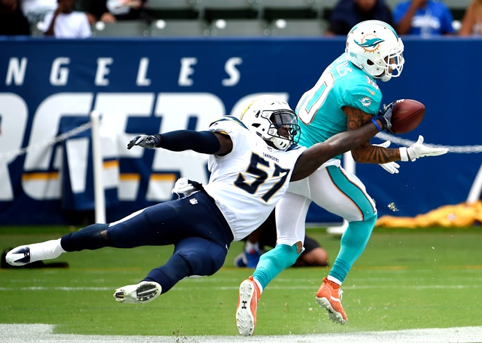 Miami Dolphins wide receiver Kenny Stills (right) makes a touchdown catch in the end zone as Los Angeles Chargers inside linebacker Jatavis Brown tries to get a hand on the ball during the second half of their NFL football game Sunday, Sept. 17, in Carson, Calif. (AP Photo/Denis Poroy)