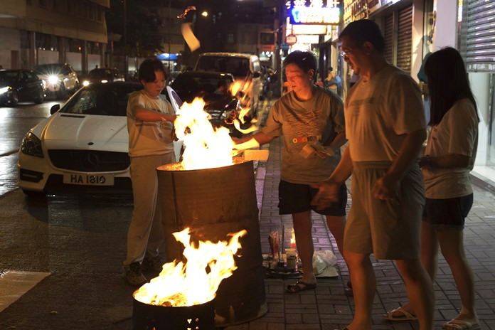 """A family burns paper money – locally known as """"Hell Money"""" – during the """"Hungry Ghost Festival"""" on a street in Hong Kong. (AP Photo/Kin Cheung)"""