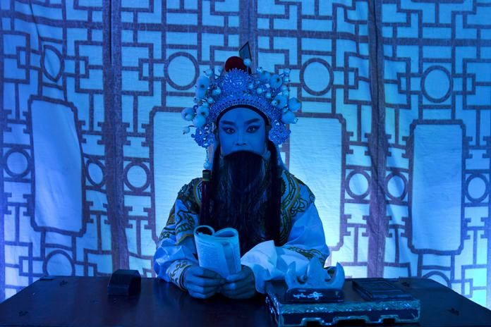 """A Chinese opera actor performs at a makeshift theater during the """"Hungry Ghost Festival"""". (AP Photo/Kin Cheung)"""