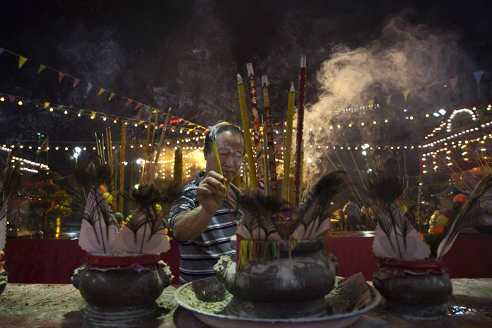 """A worshiper burns incense during the """"Hungry Ghost Festival"""" in Hong Kong. (AP Photo/Kin Cheung)"""