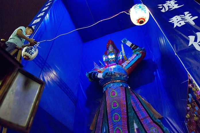 """A man hangs a lantern in front of a paper reproduction of the """"Ghost King"""". (AP Photo/Kin Cheung)"""