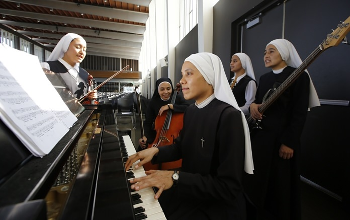 """Members of """"Siervas,"""" a Peruvian-based rock 'n' roll band comprised entirely of Catholic nuns rehearse a day ahead of their performance at the Christ Cathedral campus in Garden Grove, Calif. (AP Photo/Damian Dovarganes)"""