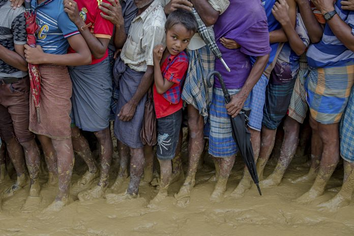 In this Tuesday, Sept. 19, 2017 file photo, a young Rohingya Muslim boy, who crossed over from Myanmar into Bangladesh, waits along with others for his turn to collect food aid near Kutupalong refugee camp, Bangladesh. With a mass exodus of Rohingya Muslims sparking accusations of ethnic cleansing from the United Nations and others, Myanmar leader Aung San Suu Kyi on Tuesday said her country does not fear international scrutiny and invited diplomats to see some areas for themselves. (AP Photo/Dar Yasin, File)