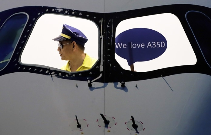 In this Wednesday, Sept. 20, 2017 file photo, a man wearing a pilot hat prepares to take a souvenir picture on a mock cockpit promoting the Airbus airliner at Aviation Expo China in Beijing. The expo features as many as 300 foreign and local exhibitors showcasing their latest aviation products. (AP Photo/Andy Wong, File)