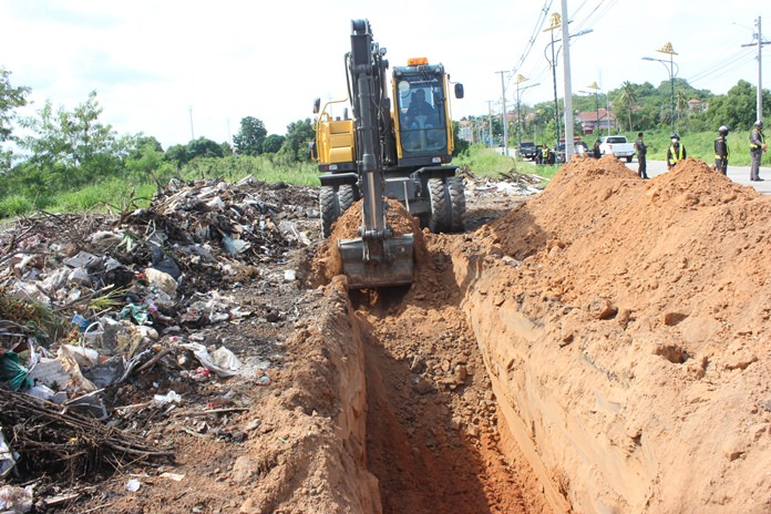 An officially hired backhoe digs a large hole to bury on site garbage dumped along a stretch of Pattanakarn Road.