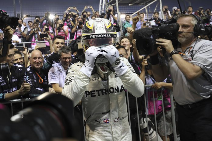 Mercedes driver Lewis Hamilton of Britain celebrates after winning the Singapore Formula One Grand Prix on the Marina Bay City Circuit Singapore, Sunday, Sept. 17. (AP Photo/Yong Teck Lim)