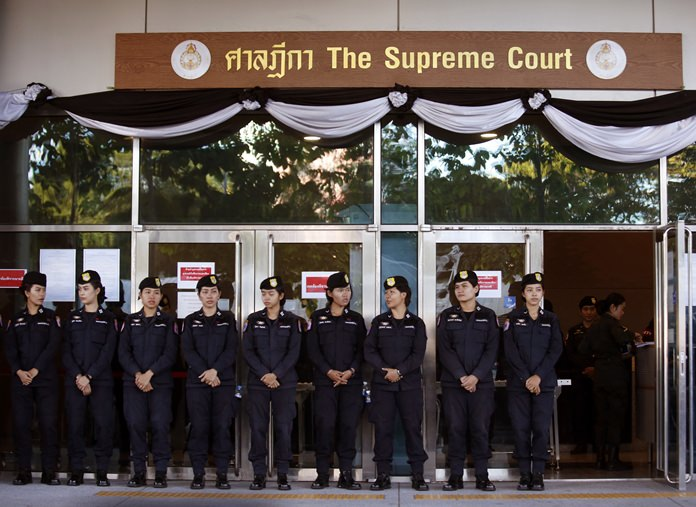 Female police officers stand guard outside the Supreme Court in Bangkok, Wednesday, Sept. 27, as the judiciary delivered its verdict on case against former Prime Minister Yingluck Shinawatra. (AP Photo/Sakchai Lalit)
