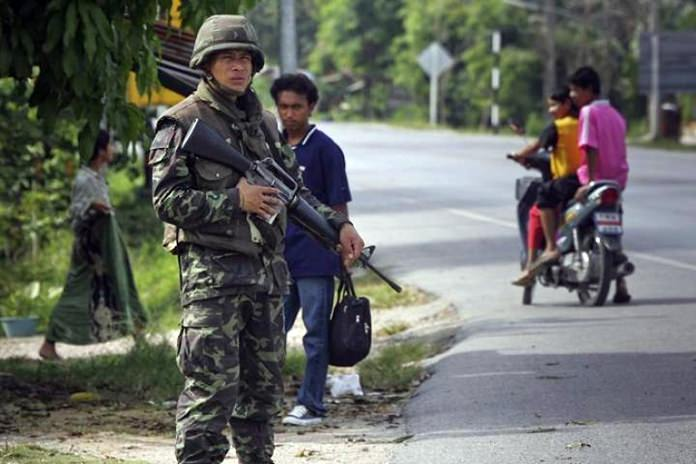 A Thai soldier mans a checkpoint as members of the public look on near Pattani, southern Thailand. (AP Photo/David Longstreath)