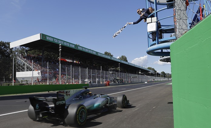 Mercedes driver Lewis Hamilton of Britain gets the checkered flag as he crosses the finish line to win the Italian Formula One Grand Prix, at the Monza racetrack, Italy, Sunday, Sept. 3. (AP Photo/Luca Bruno, Pool)
