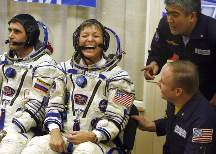 In this Wednesday, Oct 10, 2007 file photo, U.S. astronaut Peggy Whitson, center, commander of the 16th mission for the International Space Station, smiles just before the launch of the Russian Soyuz rocket at the Baikonur cosmodrome, Kazakhstan.(AP Photo/Mikhail Metzel)