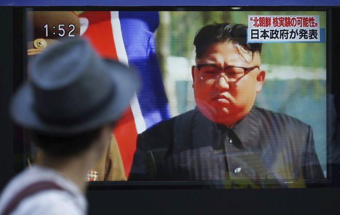 A man watches a TV news program on a public screen showing an image of North Korean leader Kim Jong Un.(AP Photo/Eugene Hoshiko)