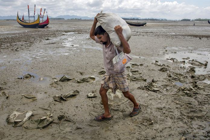 A Rohingya Muslim, who crossed over from Myanmar into Bangladesh, walks towards the nearest refugee camps carrying his belongings at Teknaf, Bangladesh, Saturday, Sept. 16, 2017. (AP Photo/Dar Yasin)