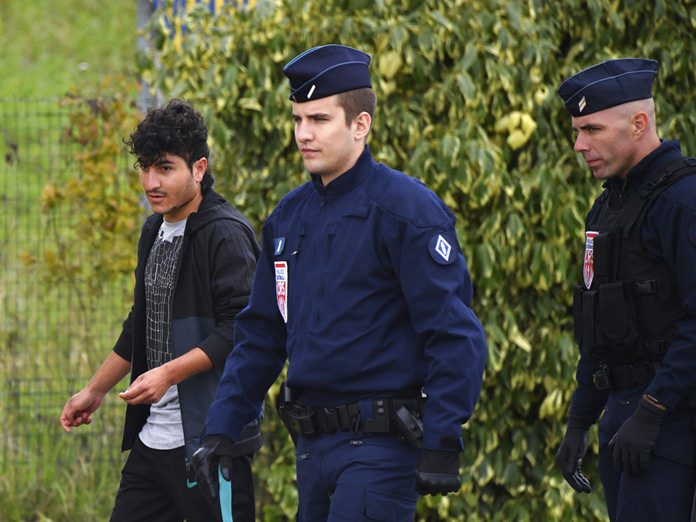 French police officers evacuate migrants from a makeshift camp in Grand-Synthe. (AP Photo)