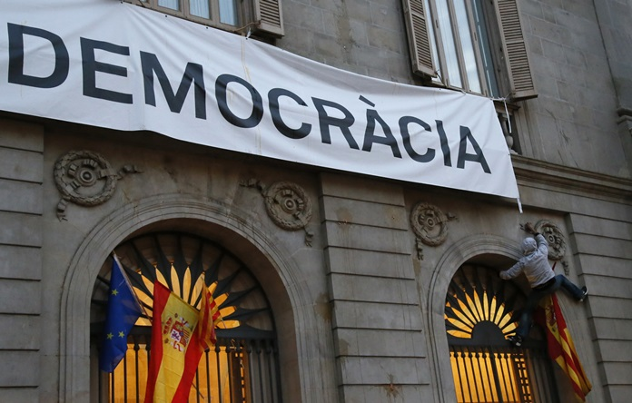 """A pro-Spanish unity demonstrator attempts to climb the facade of Barcelona City Hall to reach a banner reading in Catalan """"More Democracy"""" Saturday, Sept. 30. Catalonia's planned referendum on secession is due to be held Sunday. (AP Photo/Bob Edme)"""