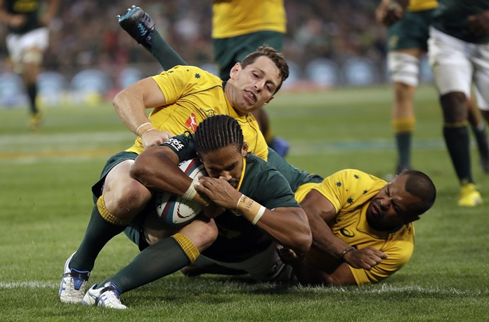 South Africa's Courtnall Skosan' front, scores a try as Australia's Bernard Foley, left, and teammate Kurtley Beale, defend during their teams' Rugby Championship match at the Free State Stadium in Bloemfontein, South Africa, Saturday, Sept. 30. (AP Photo/Themba Hadebe)